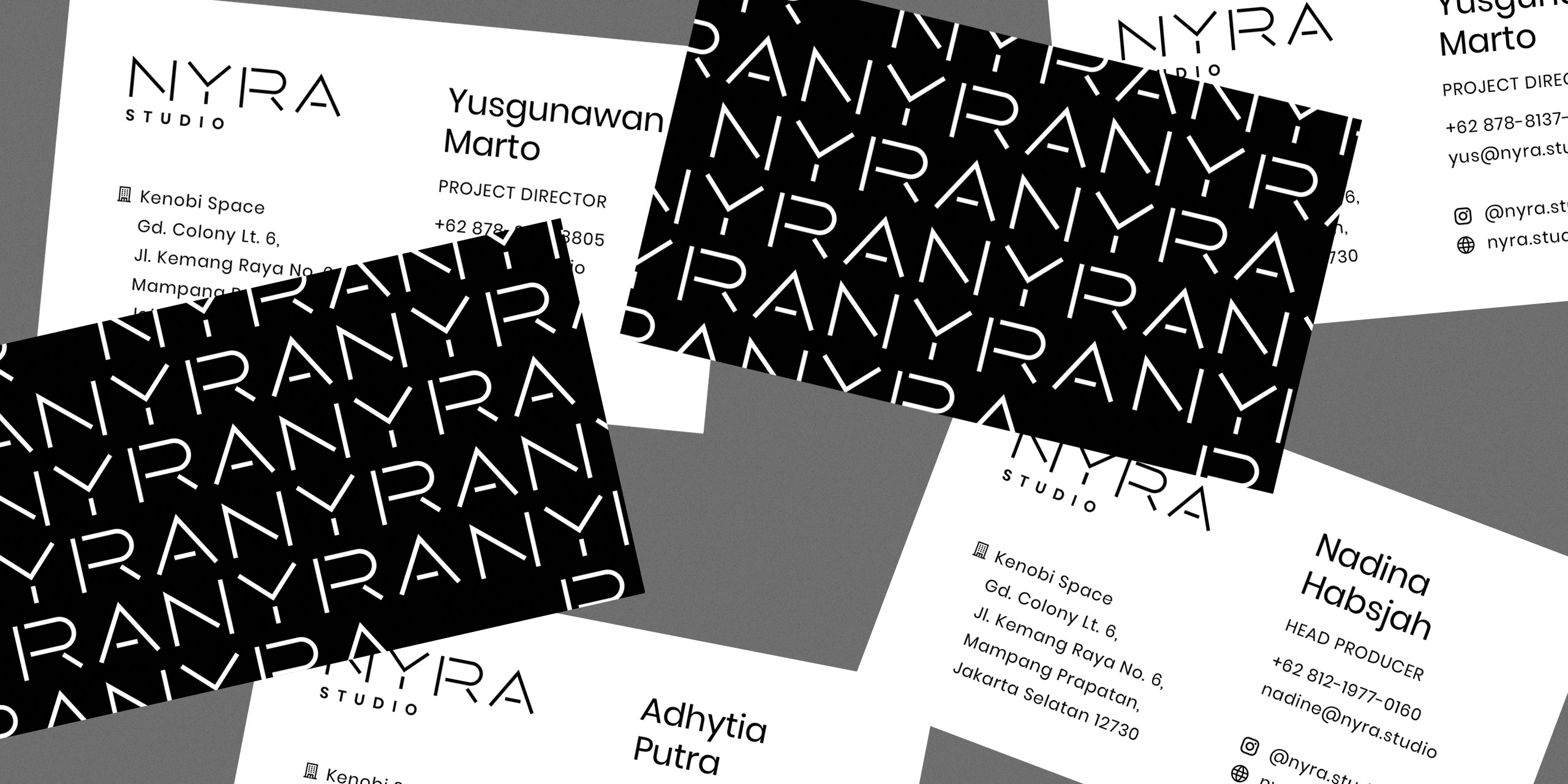 A pile of NYRA business cards, showing the back for some cards with a black background and white NYRA pattern print, and the front with NYRA members contact information